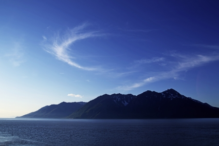 Wisp of clouds over mountains across the Cook Inlet in Alaska on a summer evening with bright blue skies. Stock Photo