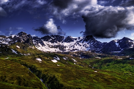 Landscape of the Talkeetna Mountains from Hatcher Pass in Alaska on a summer day with interesting clouds. Imagens