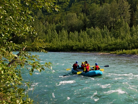 Rafting on whitewater in Sixmile Creek near Hope, Alaska on a sunny summer day.