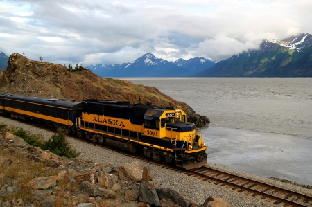 Train on the Turnagain Arm in Alaska heading towards Anchorage with clouds.