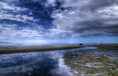 Cloud reflections in water on the beach at low tide on a summer day. photo