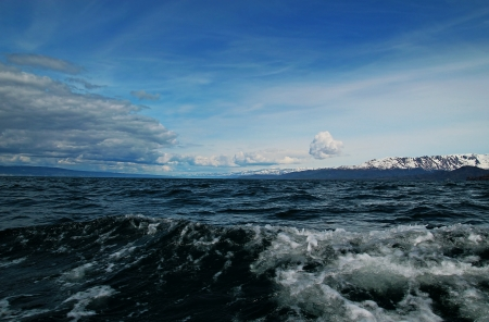 homer: Large ocean waves with clouds and blue sky in the Kachemak Bay near Homer Alaska