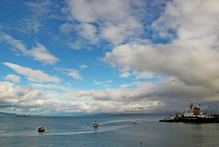 coast guard: Fishing boat moving past the Coast Guard boat in the Kachemak Bay near Homer, Alaska with interesting clouds. Stock Photo