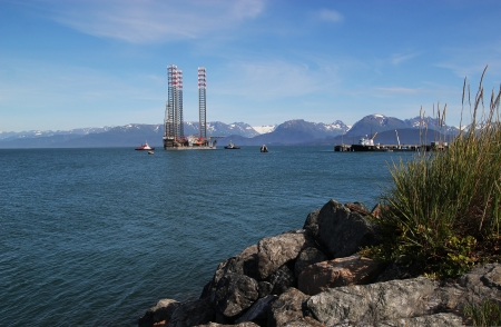 homer: Jackup oil drilling rig being moved by tug boats to the dock in Homer Alaska in summer.