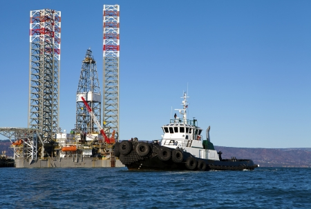 homer: Oil drilling jack up rig with a tug boat in the Kachemak Bay near Homer Alaska on a sunny day.