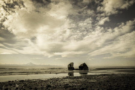Moody clouds over an Alaskan beach colorized for a vintage look.