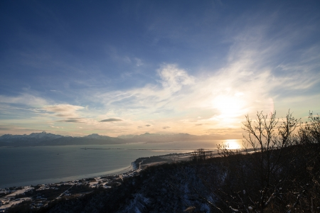 homer: View of the Kachemak Bay in Homer Alaska in winter with a setting sun.