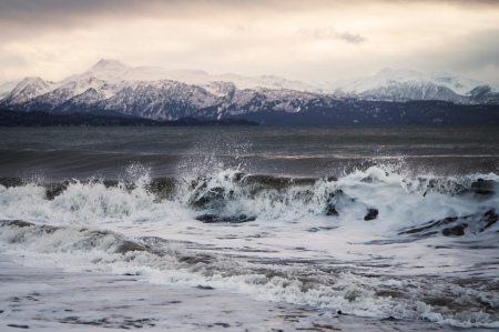 Large waves splashing  on an Alaskan beach at sunset with snow covered mountains in the distance.