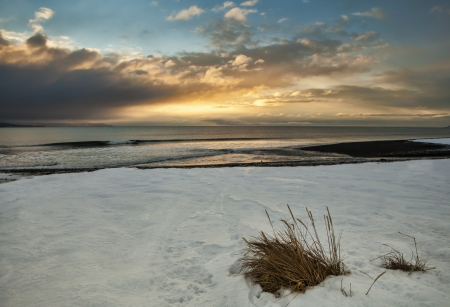 Sunset on an Alaskan beach near Homer with beach grass, snow and colorful clouds. photo