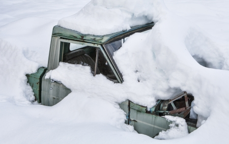 Old truck buried in deep snow.