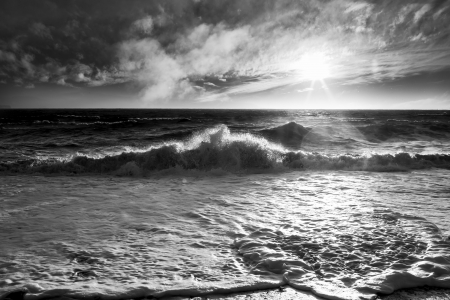 Ocean waves with a sunburst and lens flare on a windy day in black and white.