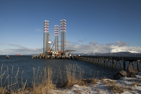 Jack-up rig parked at the harbor in Homer Alaska in winter with a tanker in the background.