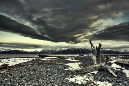 Storm clouds over the Kachemak Bay in Alaska with patches of snow and driftwood on the beach. Stock Photo
