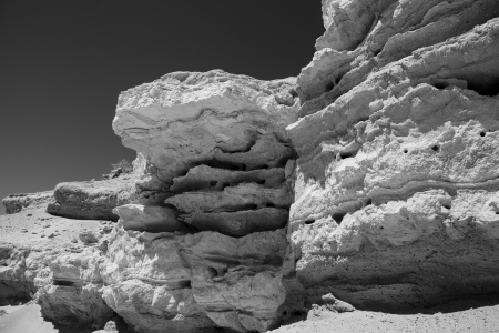 Rock patterns in an eroded desert cliff in black and white.