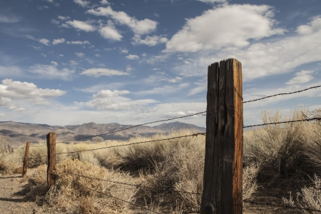 Fence post with barbed wire fencing in high desert of the west with blue sky and puffy clouds. photo