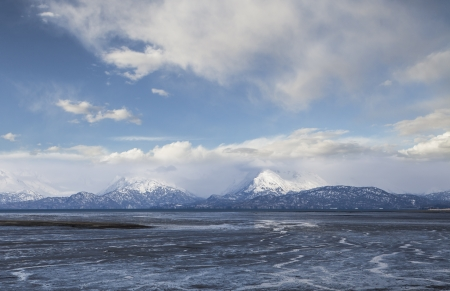 mud and snow: Patterns in Mud Bay at low tide near Homer Alaska with snow covered mountains and clouds.