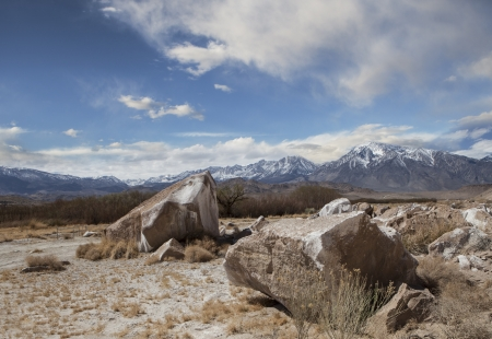 drained: Large rocks on a former lake bed in the Eastern Sierras drained for LA water with clouds and blue sky.