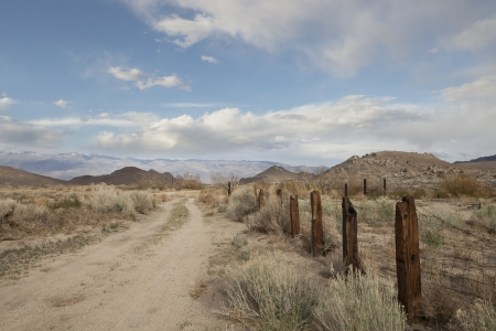 Desert dirt road leading off to the mountains with an old fence and cloudy skies  photo