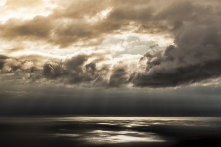 parting the sea: Hole in a dark storm cloud with sun breaking through with light rays on the water of the bay. Stock Photo