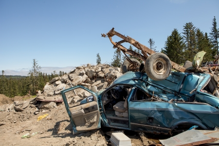 Smashed car after an accident in a dump with other trash on a sunny day. Stock Photo