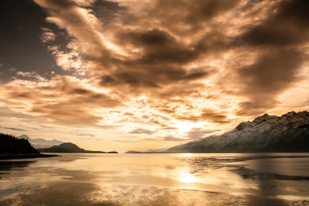 alaska scenic: Sunset over the scenic Chilkat Inlet in Southeat Alaska with snow covered mountains in the background.