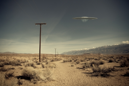 Low flying UFO spaceship hovering over a desert dirt road near a telephone pole with a vintage look. Stock Photo