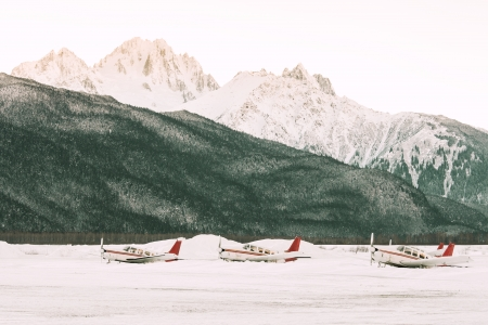 grounded: Three small planes at an Alaskan airport in winter with snowy mountains in the background and a pink sunset glow.