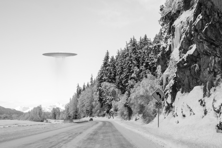 winter road: UFO space ship hovering over an Alaskan road in winter with a car in the distance.