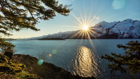 hemlock: Resplandor solar sobre montañas cubiertas de nieve en un día soleado de invierno en el sudeste de Alaska, cerca de la entrada de Chilkat.