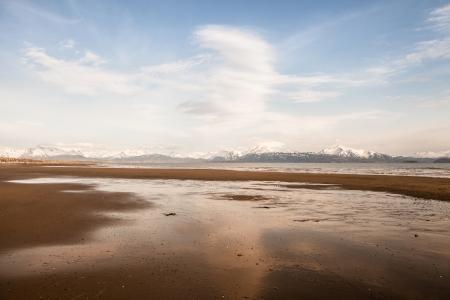 homer: Empty sandy Alaskan beach near the Kachemak Bay with blue sky and clouds.