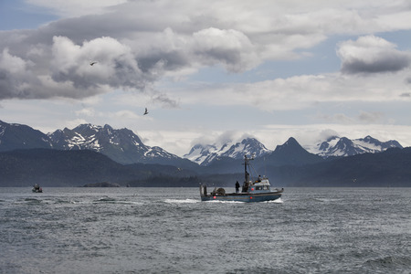 Fishing trawler in the Kachemak Bay near Homer Alaska with clouds and birds. photo