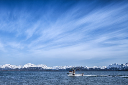 Small fishing trawler moving through the Kachemak Bay near Homer Alaska with blue sky and interesting clouds. photo