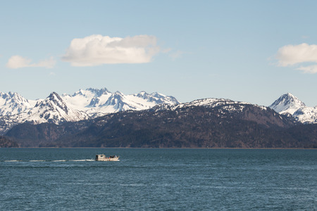 Fishing boat in the Kachemak Bay with a puffy cloud. photo