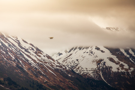 small plane: Small plane flying through mountains near Moose Pass Alaska with storm clouds.