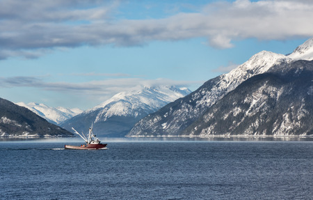 Fishing boat in Portage Cove heading towards the Lynn Canal on a sunny winter day.