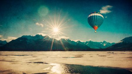 Hot air balloon flying over ice in an Alaskan winter with textures added for an artistic look.