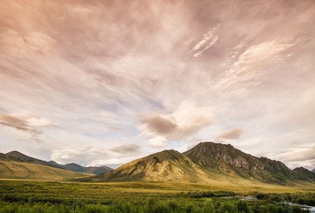 Sunset clouds and magical evening light in the Tombstone range off the Depster Highway in the Yukon Terriroty in Canada in summer. Stock Photo