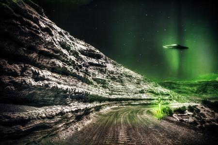 raumschiff: Alien auf einem einsamen Feldweg in der Nacht mit ein UFO fliegen in den Hintergrund. Lizenzfreie Bilder