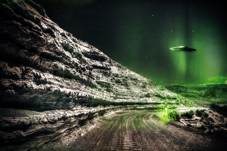 Alien on a lonely dirt road at night with a UFO flying off in the background.