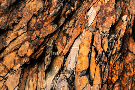 Abstract rock patterns  flaking off a cliff by the sea. Imagens