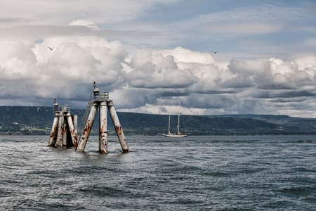 homer: Storm clouds over the Kachemak Bay in Alaska with a sail boat and old pier pillars.