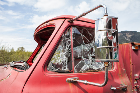 antique fire truck: Vintage fire truck with smashed windows against blue sky with clouds. Stock Photo