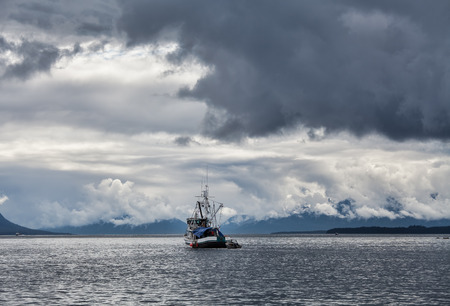 Old fishing boat in Southeast Alaska with stormy skies.