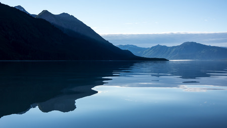 southeast alaska: Mountains reflected in calm water in evening  on the Chilkat Inlet in Southeast Alaska.