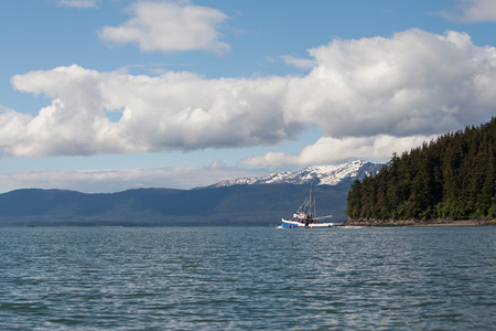 Southeast Alaskan fishing trawler heading out on a summer day. photo