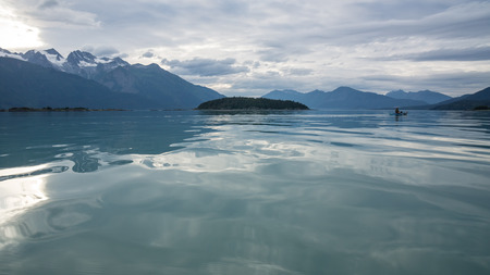 southeast alaska: Kayaking in Southeast Alaska on a calm evening near the Chilkat Inlet  with Kochu Island in the distance.