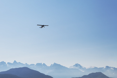 hazy: Small plane flying over hazy mountains in Southeast Alaska with bright blue sky  Stock Photo