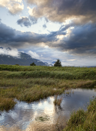 southeast alaska: Dramatic clouds at sunset reflected in a pool of water in Southeast Alaska. Stock Photo