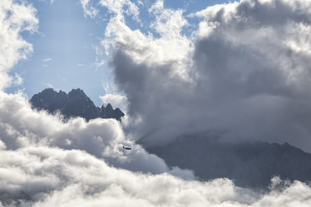 small plane: Small plane flying through big clouds in the rugged mountains of Southeast Alaska.