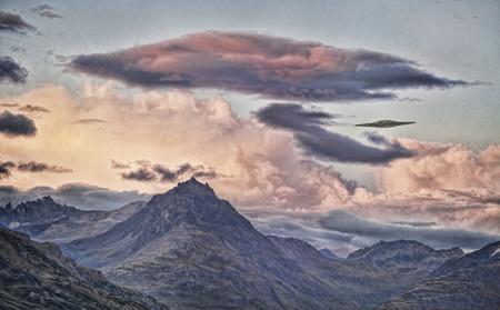 disco volante: UFO disco volante sopra le montagne con le nuvole tramonto trattati con texture per un look artistico. Archivio Fotografico